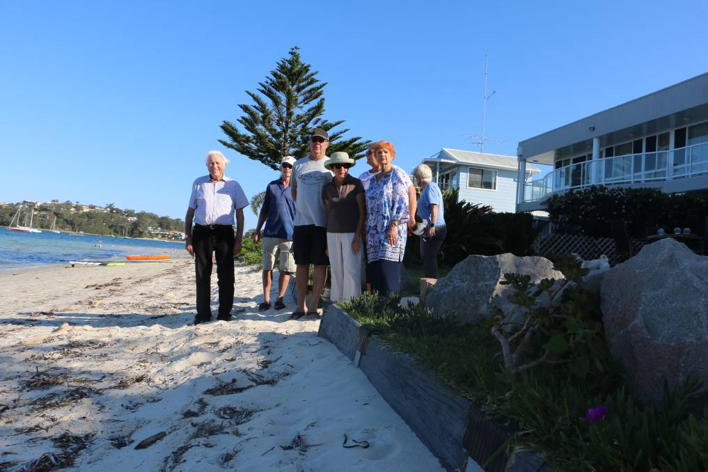 SEA WALL: Residents of Soldiers Point Road, with John Young at left, whose properties back on to the foreshore and their environmentally-friendly sloping wall.
