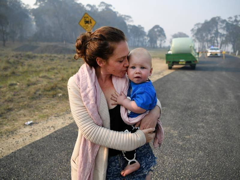 Wytaliba resident Storm Sparks and son Zeke Bacon had to wait as bushfires raged near their home.